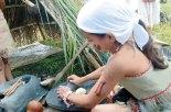"""Esta niña """"Chorotega"""" utiliza la piedra de moler como lo hacían ellos."""
