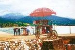 """Esta imagen fue tomada en  Omoa  """" El Vendedor""""  al fotógrafo le llamó la atención el paragua de  colores brillantes , la carreta y la calle empedrada que conduce al muelle."""
