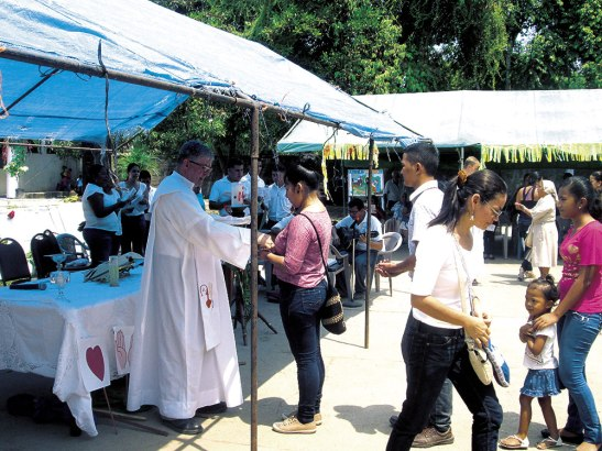 Monseñor Solé reparte la comunión durante la Eucaristía.