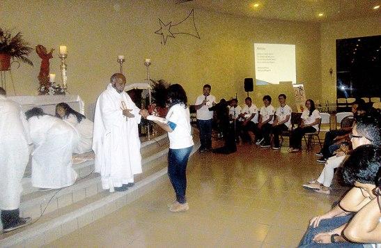 El Padre  Ovidio recibe las ofrendas de parte de una joven  participante en la jornada.