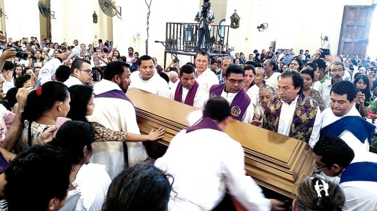 Sacerdotes y acólitos cargan los restos del párroco Senis.