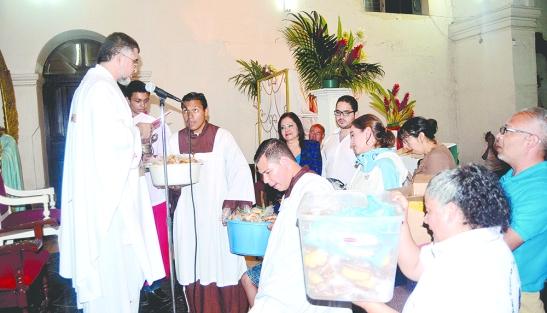 """Momento que Fray Rocael de la parroquia Inmaculada bendice """"el Pan de San Antonio""""."""